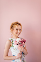 c7938bf64a Beautiful young girl with blonde hair is standing with a bouquet of color  on a pink
