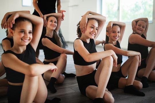 Teacher and group of children exercising dancing and ballet in dance school
