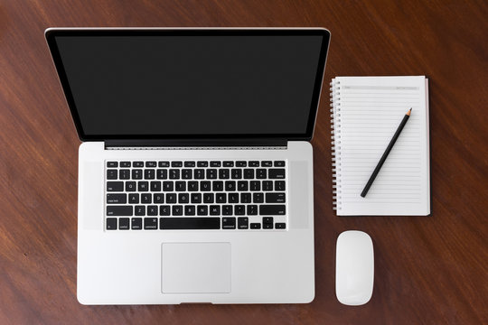 Laptop with blank screen and notepad on table top view copy space mockup