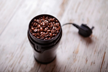 Coffee beans in a coffee grinderon a white wooden floor