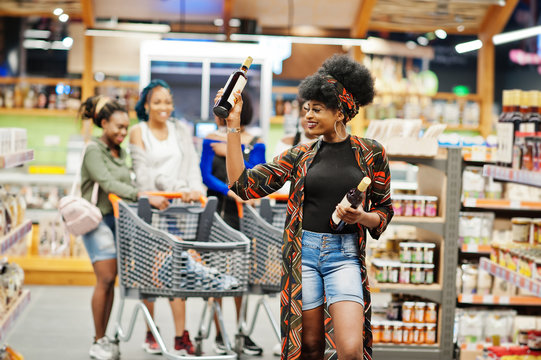 African american woman choose wine at supermarket against her afro friends with shopping cart.