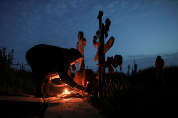 A woman lights candles at the grave of a departed relative in a cemetery 50 kilometers south west of Romanian capital Bucharest, in the early hours of Maundy Thursday