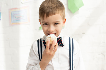 adorable preteen boy in bow tie eating cupcake and looking at camera