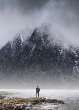 Man stood in front of foggy misty mountain to give scale of mountain size and concept of overpowering challenge