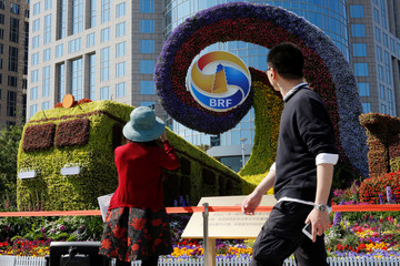 Woman takes pictures of a flower installation marking the Belt and Road Forum in Beijing