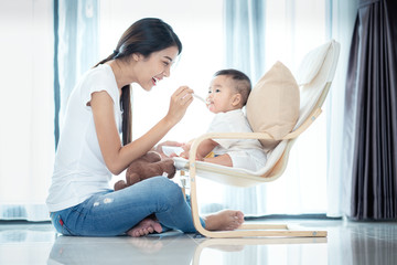 Asian mother feeding to her baby