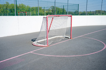 The player in the inline skates stands at his gate. Before the big tournament. Empty ice hockey playground - view from behind the gate. Before The Match On Top Of Street Hockey.