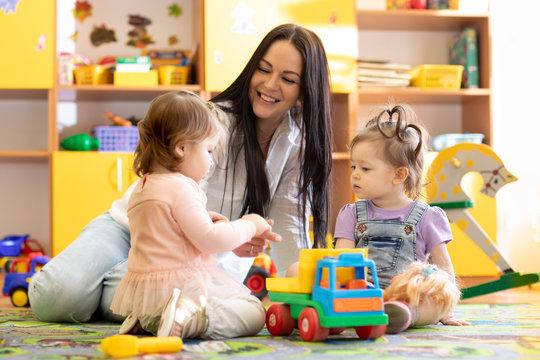 Nursery children playing with teacher in kindergarten