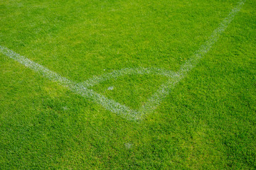 Soccer field or Football field. Close up corner of white line paint on green synthetic lawn football,soccer field.