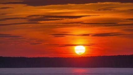 Fotobehang - Sunset sun setting behind distant forest on winter lake shoreline. Timelapse, 4K UHD.