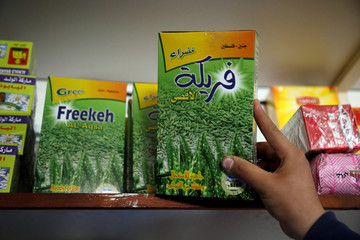 Palestinian man shows a packet of freekeh, a Middle Eastern cereal dish, in a grocery in Tubas in the Israeli-occupied West Bank