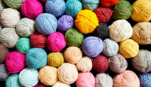 Colorful background made of many wool yarn balls.