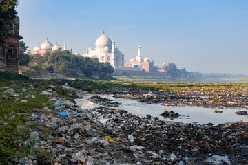 Indias contrast of ugly pollution and stunning beauty, The banks of Yamuna River polluted with garbage and beautiful Taj Mahal in the background Fototapete