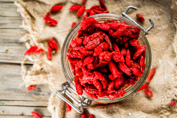 Dried goji berries in little jar, wooden background copy space