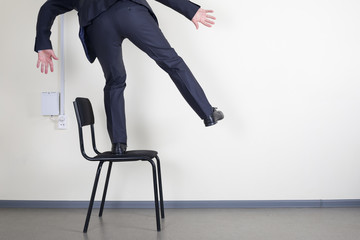 Businessman balancing while standing on an office chair against the wall with space for text.
