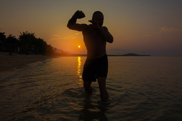 Male silhouette jumping in the water at the sea at sunset