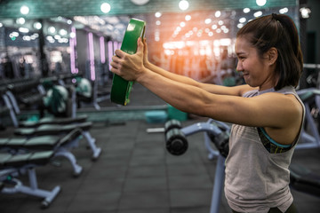 Young fit woman doing workout with weight plate at the gym