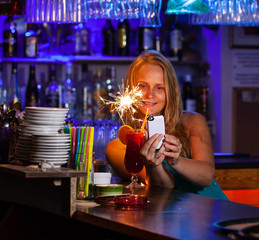 A young woman sitting in a bar and photographing her cocktail with a sparkler on her smartphone
