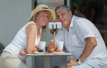 A middle-aged couple makes a selfie with a selfie-stick,  while having drinks and desserts at a street cafe