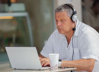 A middle-aged man sitting at a table outdoor with an opened laptop and a headset on his head