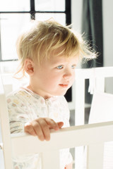 An awaking baby girl, standing in her cot