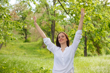 Happy young woman enjoying nature in a park. Beautiful Girlin white with arms up. Outdoor image. Freedom concept