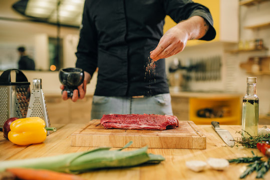 Male person marinating raw meat on wooden board