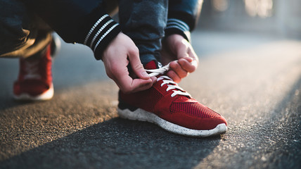 Close-up of sportsman tying sneakers. Unrecognizable man stopping lacing shoe outdoors. Athletic shoes concept.