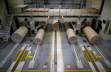An employee works on giant reels of paper inside the carboard box manufacturing company DS Smith Packaging Atlantique in La Chevroliere near Nantes