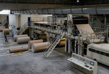 Employees work on reels of paper inside the carboard box manufacturing company DS Smith Packaging Atlantique in La Chevroliere