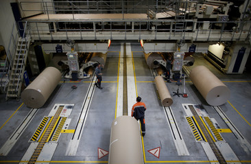 Employees work on giant reels of paper at the carboard box manufacturing company DS Smith Packaging Atlantique in La Chevroliere
