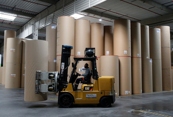 An employee transports a giant reel of paper at the carboard box manufacturing company DS Smith Packaging Atlantique in La Chevroliere near Nantes