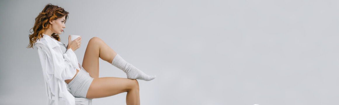 panoramic shot of beautiful woman sitting on chair and holding cup on grey