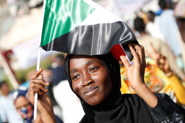 A Sudanese protester holds a national flag outside the defense ministry compound in Khartoum