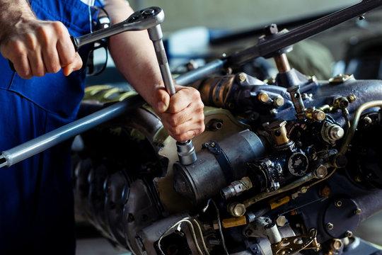 Aircraft mechanic repairing jet engine