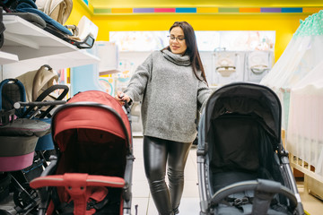 Pregnant woman looking for pushchair in store