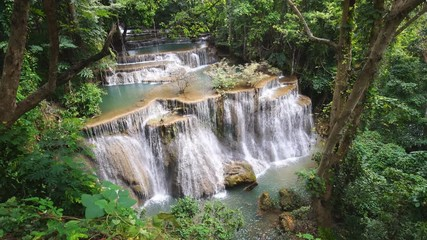 Wall Mural - Waterfall flow standing with forest enviroment from high angle view in thailand, called Huay orHuai mae khamin in Kanchanaburi Provience, Zoom in.