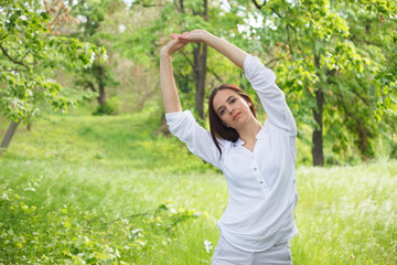 Young woman enjoying nature in a park. Beautiful Girlin white with arms up. Outdoor image.