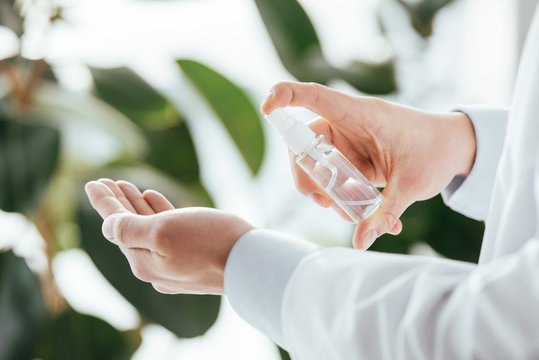 cropped view of doctor applying antibacterial spray on hand in clinic