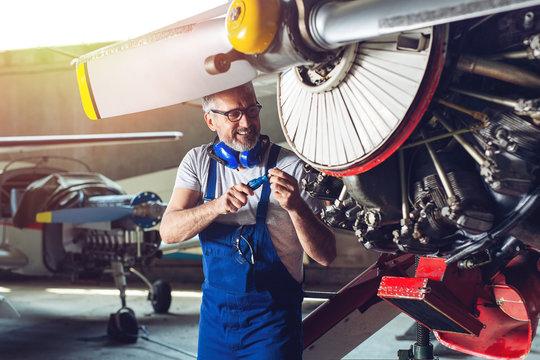 Plane Maintenance Engineer Repairing Engine