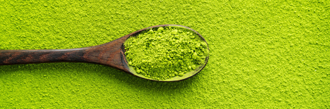 Top view of wooden spoon with green tea Matcha on powder maccha texture background. Long wide banner with copy space.