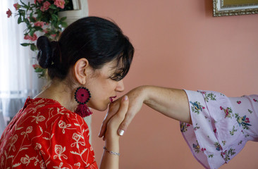 Woman kissing parent's hand for traditional act of respect. Female kissing old people's hand on religious holidays (Victim Feast or Ramadan Feast). Respect for mother, father, grandmother, grandfather