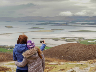 Mother and daughter taking picture of view from Croagh Park , Ireland,