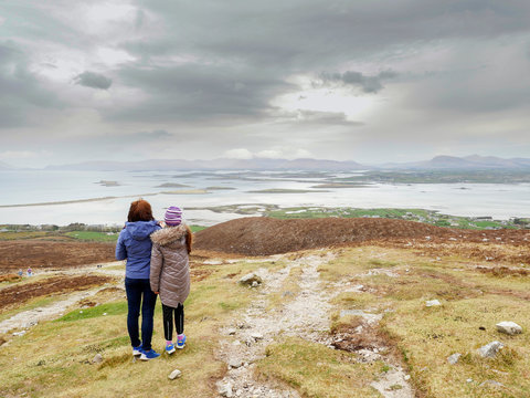 Mother and daughter looking at beautiful view of Westport area Ireland.Cloudy sky,