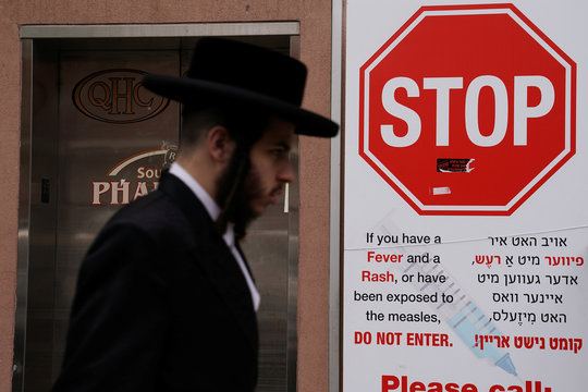 A man walks past a sign advising about a measles outbreak in the Brooklyn Borough of New York