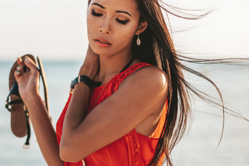 close up of a beautiful asian filipino girl with smooth tan skin and her hair blowing in the wind while holding a sandal and wearing an orange sleeveless blouse on the sandy beach