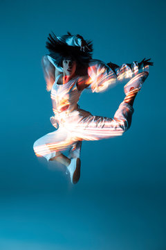 Pretty young woman in sportswear leaping up and looking at camera on blue background