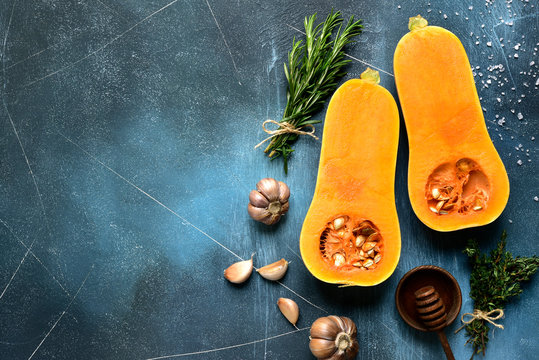 Halves of raw organic butternut squash with ingredients for making . Top view with copy space.