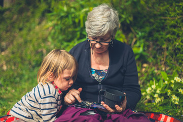Toddler and grandmother using smartphone in nature