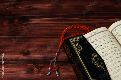 Islamic Holy Book Quran with rosary beads on wooden table background